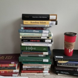 A stack of books about history of science, India, and religion.